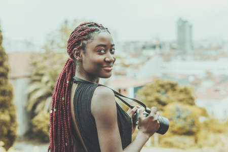 A dazzling young African tourist woman photographer with maroon colored braids is staying on some observation point, smiling and holding a camera in her hands; a cityscape in the defocused background