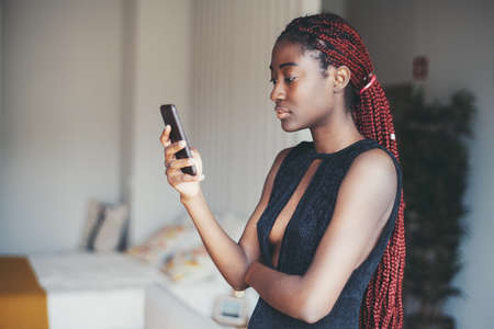 A lovable young black female with maroon color braided afro hair and in a dark low-cut dress is marking up a meeting with a friend via a smartphone in her hand while standing indoors of her apartment
