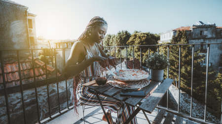 A ravishing young black woman is having lunch and cutting to pieces a delicious pizza while sitting at the table with a glass of wine on a large balcony of her house with a cityscape around her
