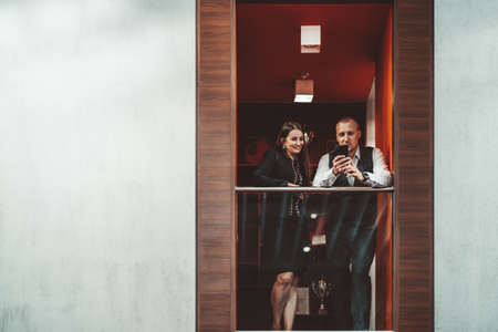 Two entrepreneurs having a business talk while standing on the office balcony: businessman is showing a funny message on the screen of a cellphone to his female colleague; copy space place on the left