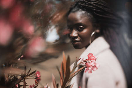 A true tilt-shift portrait of a ravishing young black woman with braids looking at camera while standing in a park with a selective focus on part of her face and the pink flower in front of her