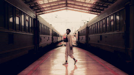 A dark pinkish interior of a railway station depot with charming elegant black tourist girl in spectacles and a white trench standing on a railroad platform between two modern high-speed trains Foto de archivo