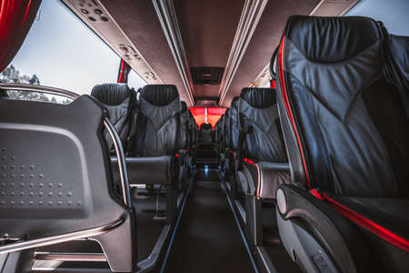 An empty interior of a regular intercity bus with rows of leather numbered seats with red borders