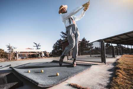 A handsome mature bearded retrosexual black guy in trousers with suspenders, white shirt, and hat is got the stance and hit the ball with a golf club on a golf field; several yellow balls near him 写真素材