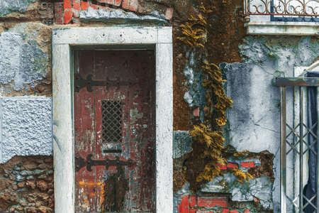 Texture of an old flaked stone facade wall of an antique house with a doorway, red bricks, stones, and cracked plaster, old dark-red door with wrought iron hinges and a lattice in the center