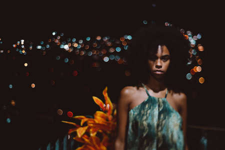 A shot in a dark key of a young ravishing Brazilian female in a simple sundress standing on her house balcony at warm night, with a cityscape behind her, totally blurred into bokeh bulbs