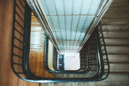 View from above with a shallow depth of field of a long stairwell going down in a spiral, an old residential building with a metal railing and a lift shaft in the center, selective focus in the middle