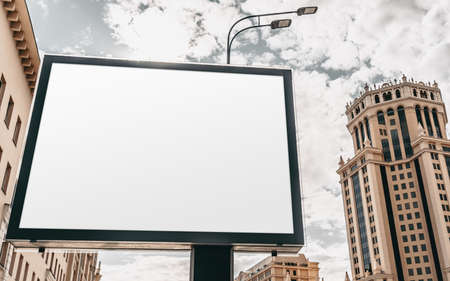 Mock-up of a big empty advert billboard in city settings above the street; an empty information banner template outdoors; an outdoor blank poster placeholder mockup with a skyscraper behind it