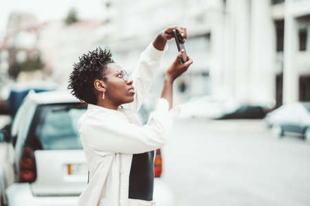A profile portrait of a young ravishing black female hipster in elegant spectacles and a white trench taking pics outdoors using a camera of her smartphone near the road with parked cars; a bright day