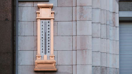A giant gilded mercury thermometer at around 25 with a scale from minus 54 to plus 54 degrees around zero, hanged on the stone wall on the street to show an outdoor air temperature