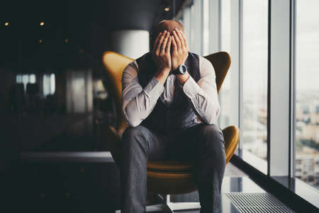 A man entrepreneur is in sorrow because of his dismissal; a businessman on an orange armchair near an office window covered his face with his hands after learning about the bankruptcy of the company