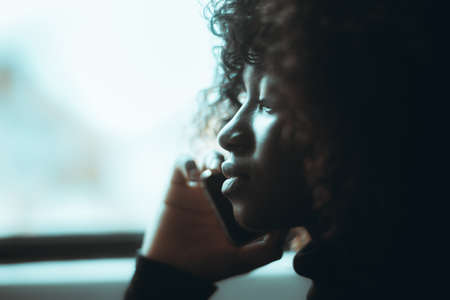 A profile portrait with a shallow depth of field of a ravishing young black female with curly hair talking on the phone near the window