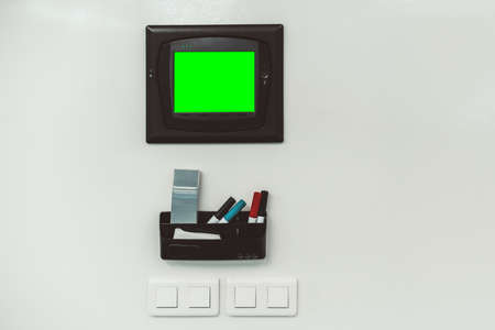 A white wall or board in an office for drawing or sketching, the device to control room lighting and air conditioning in the middle with a green screen template, a box with multi-colored markers below