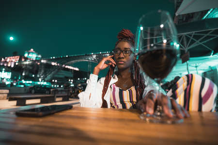A pensive young ravishing black woman in eyeglasses and with braids is chilling in a night outdoor cafe with a glass of red wine in the defocused foreground; an arc bridge in the background, full moon