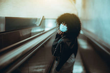 True tilt-shift portrait of a black female in a virus protective facial mask, descending to the metro on the escalator; a curly-hair African woman in an anti-virus mask is going down the subway