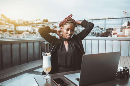 A portrait of a ravishing young black woman freelancer adjusting her hair while sitting in an outdoor restaurant on the roof and working on a laptop; a glass of a delicious cocktail next to her