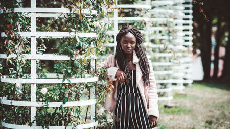 Portrait of a ravishing young African female with huge earrings and a nose piercing, in a striped jumpsuit and pink demi-season coat, leaning against the metal part of a vertical flower bed with roses