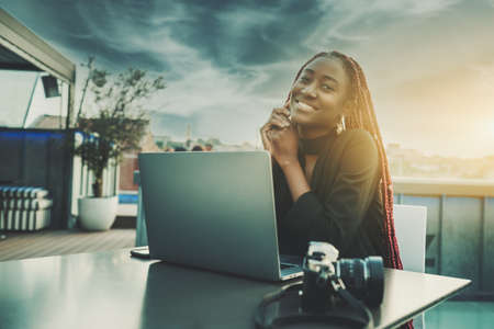 A portrait of a ravishing cheerful young black female freelancer smiling and enjoying an evening while sitting at the table of a street cafe on the roof with a laptop and film camera in front of her