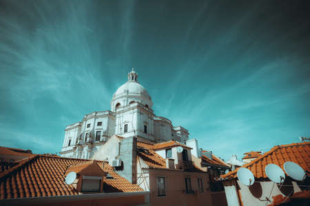 A wide-angle cityscape of a residential district of Lisbon, Portugal with a The Church of Santa Engracia or another name National Pantheon, with a cloudscape in the form of diverging emanations Banco de Imagens