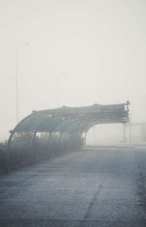 A vertical foggy scenery with a morning view of a parking on the territory of a filling station with a curved metal roof of a canopy against the rain