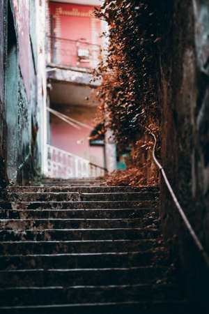 A stone dark stairway leading to a yard with a reddish facade in the defocused background, shallow depth of field, selective focus on the last stony steps