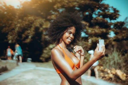 Portrait of laughing young flirtatious African-American female in a swimsuit having video call with her boyfriend via cellphone while standing in a beach area or a tropical resort near a coastal park