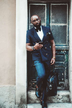 Vertical view of a dapper bald mature black guy with a beard, in a suit with a bow tie and leather bag, leaning against the wall on the stoop of an antique building after leaving the wooden door