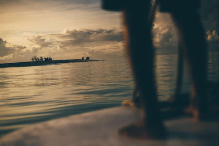 A stunning sunset seascape with shallow depth of field and selective focus on a group of people on a resort island in the background; feet of a man steering a boat in a defocused foreground, Maldives
