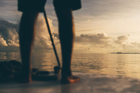 A stunning sunset seascape with shallow depth of field and selective focus on a small island in the background; legs of a man steering a boat in a defocused foreground, Maldives Stockfoto