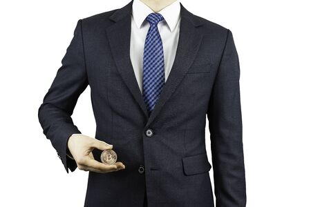 A person wearing a suit and holding a bitcoin in his hand. Stock Photo
