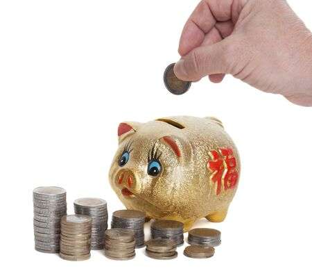 coining: Golden piggy bank is fed with a coin