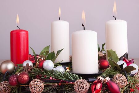 Advent wreath decorated for Christmas with lighted candles