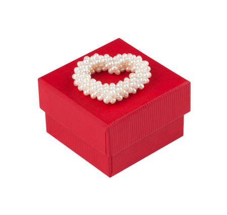 Red gift box with a heart of pearls in front of white background  photo