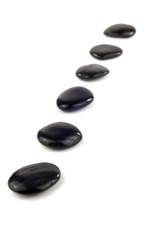 Black pebbles in a row in front of white background photo