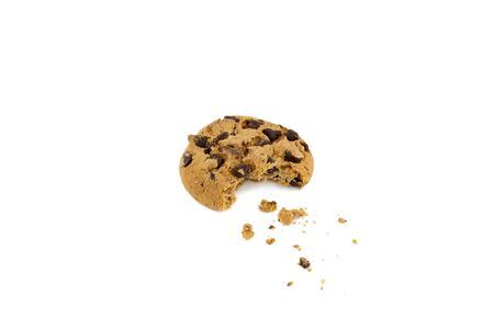 Chocolate chip cookie with bite taken out and crumbs in front of white background photo