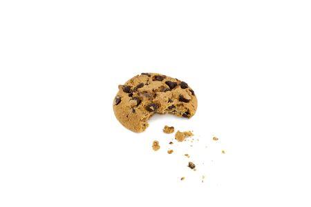 Cioccolato chip cookie con morso fuori e briciole di fronte a sfondo bianco