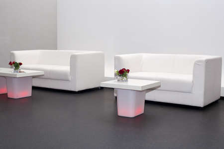 White sofas with red illuminated coffee tables photo