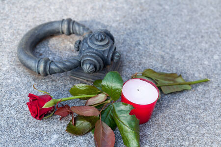 Close-up of tombstone with single rose and candle photo