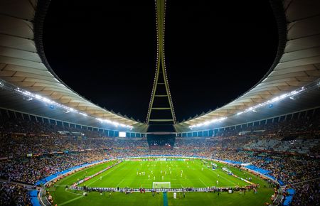 Panoramic photo showing a full Moses Mabhida stadium with the arch lights on, in perfect symmetry, during the 2010 Fifa world cup