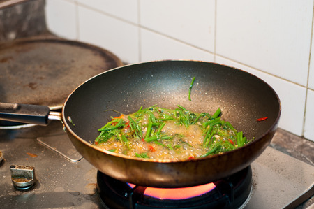 unclean: Pan is cooking on the gas stove unclean around in the pan have the food fried vegetables