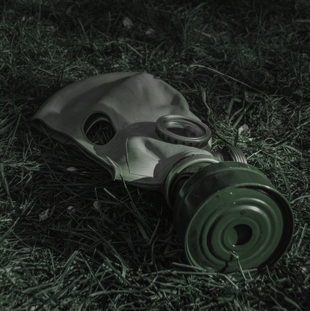 gloom: The old Soviet gas mask on the grass in the gloom of night Stock Photo