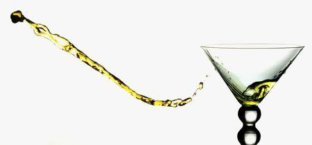 Yellow liquid splashing horizontally out of a martini glass. Stock Photo