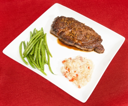 Steak au Poivre with haricots verts and bacon and red pepper risotto photo