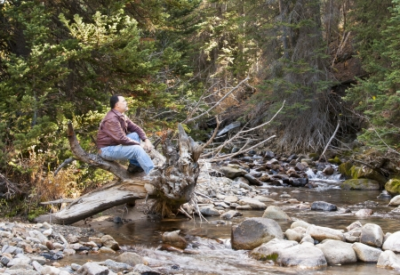 A man sitting on a log looking up over a stream running through the woods in Little Cottonwood Canyon in Utah photo