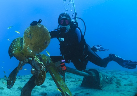 Woman scuba diver on the propeller of the Gregory, a wreck in St Maarten Stock Photo