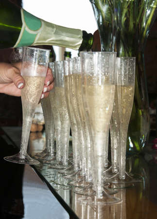Don t mind if I do - a line of champagne glasses being filled as one is taken