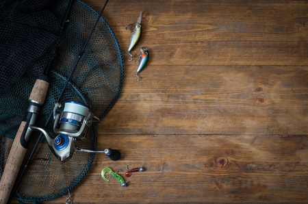 Fishing tackle - fishing spinning, hooks and lures on a darken wooden background. Top view.