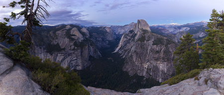 A panorama shot from Glacier Point down into the famous valley of Yosemite National Park shortly after the sun has set. On the right is the Half Dome.
