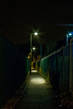 An alleyway at night lit by street lamps Stock Photo