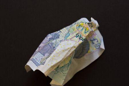 scrunched: A crumpled British five pound note